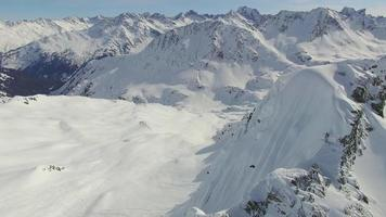 Aerial shot of skiers skiing from the top of a mountain. video