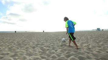 un garçon frappe un ballon de football sur la plage au coucher du soleil. video