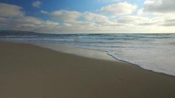 foto de rastreamento das ondas do mar, praia e cais ao pôr do sol. video