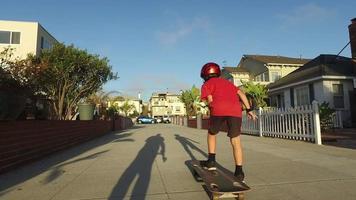 een jongen die skateboardt in een buurt. video