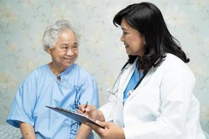 Doctor talking about diagnosis and note on clipboard with Asian senior or elderly old lady woman while lying on bed in nursing hospital ward, healthy strong medical concept. photo
