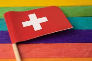 bandera de suiza en el fondo del arco iris símbolo del movimiento social del mes del orgullo gay lgbt la bandera del arco iris es un símbolo de lesbianas, gays, bisexuales, transgénero, derechos humanos, tolerancia y paz. foto