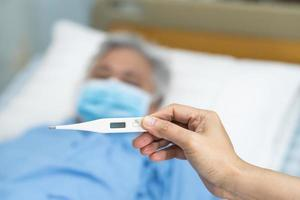Doctor holding digital thermometer to measures asian senior or elderly old lady woman patient wearing a face mask have a fever in hospital, healthy strong medical concept. photo