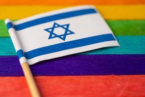 bandera de isarael en el fondo del arco iris símbolo del movimiento social del mes del orgullo gay lgbt la bandera del arco iris es un símbolo de lesbianas, gays, bisexuales, transgénero, derechos humanos, tolerancia y paz. foto