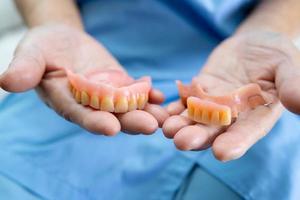 Paciente asiático mayor o anciano sosteniendo para usar dentadura en la sala del hospital de enfermería, concepto médico fuerte y saludable foto