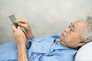 Paciente asiático mayor o anciano mujer sosteniendo en sus manos tableta digital y leyendo correos electrónicos mientras está sentado en la cama en la sala del hospital de enfermería, concepto médico fuerte y saludable foto