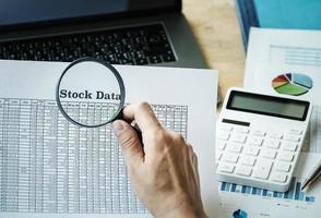 Businessman using magnifying to review balance sheet photo