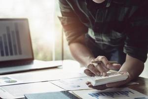 Businessman using calculator to review balance sheet photo
