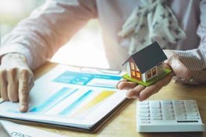 Agente de bienes raíces discutiendo préstamos y tasas de interés para comprar casas. foto