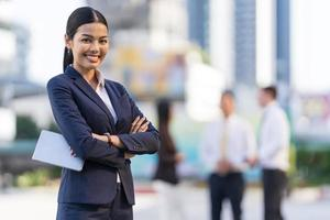 Portrait of smiling businesswoman arms crossed while standing in front of modern office buildings photo