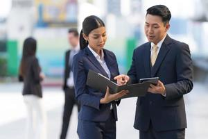 Mature businessman using a digital tablet to discuss information with businesswoman photo