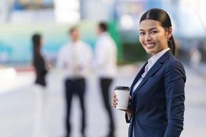 Portrait of smiling business woman holding a coffee cup photo