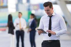 Businessman standing with using a digital tablet photo