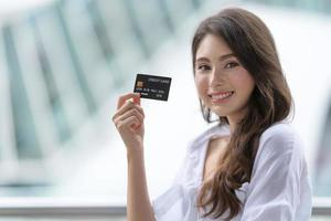 Black Friday concept, Woman holding credit card and smiling near the store photo