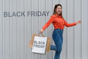 Retrato al aire libre de mujer feliz sosteniendo bolsas de la compra y cara sonriente en el centro comercial foto