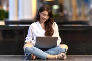 Happy young woman sitting on the floor with using laptop photo
