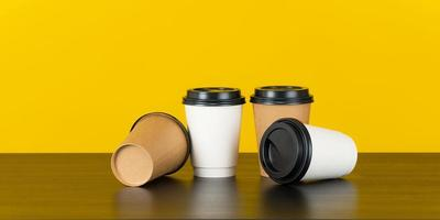 Blank paper coffee cup set on yellow background photo