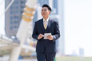 Portrait of smiling businessman using a tablet photo