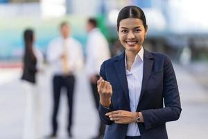 Portrait of smiling business woman while standing in front of modern office buildings photo
