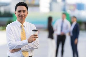Portrait of smiling businessman holding a coffee cup while standing photo