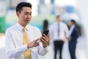 Portrait of smiling businessman using a phone photo