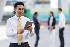 Portrait of smiling businessman looking at tablet photo