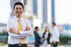 Portrait of successful businessman standing with arms crossed photo