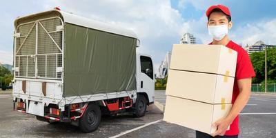 Repartidor empleado en camiseta roja uniforme mascarilla con caja de cartón vacía foto