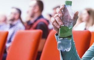 hombre de negocios en conferencia sosteniendo y bebiendo botella de agua. foto