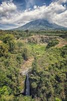 paisaje indonesio en el centro de jave. vista del volcán merapi y la cascada air terjun kedung kayang foto