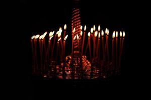 Many candles burning at night on the black background in church. Candle flame set isolated in black background. Group of burning candles in dark photo
