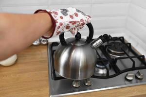 Man hand in mittens holding metalic kettle in the kitchen. photo