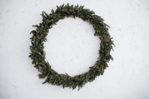 Christmas big wreath is Isolated on a stone white background. Round green wreath. natural decor. Holidays. Traditions. photo