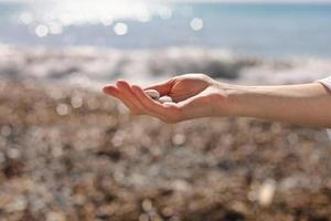 female hand holding small pebble stones in hand near blue sea on a beach background, picking up pebbles on the stone beach, round shape pebbles, summer vacation souvenir, beach day, selective focus photo