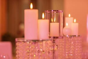 candles on a glass candlestick. Burning candle in a round glass candlestick with decorative seashells photo