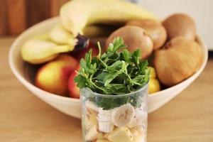 Vaso de delicioso yogur con menta y fresas frescas, plátano, lima, nectarina en una canasta de mimbre sobre una mesa de madera foto