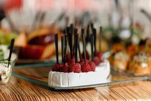 abastecimiento. alimentos para fiestas, fiestas corporativas, conferencias, foros, banquetes. diferentes tipos de queso caro con frambuesas. enfoque selectivo foto