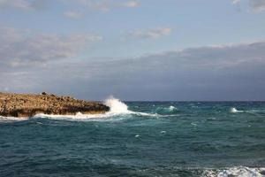 Waves hitting the rocky cliffs in a beach located in Cyprus,This weather might be dangerous for water sports but simultaneously the waves and their splashes are pretty and wild. photo
