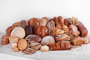 Different types of baked goods on linen and white wall background photo