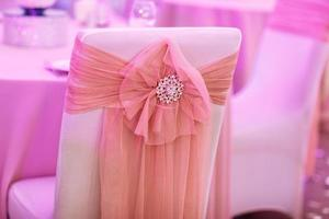 The chairs with bows and jewerly in the resturant on wedding day photo