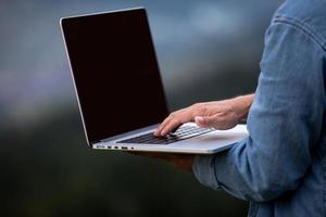 Man working outdoors with laptop in mountains. Concept of remote work or freelancer lifestyle. Cellular network broadband coverage. internet 5G. photo