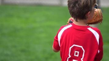 en pojke övar att spela fångst på ett litet basebollfält. video