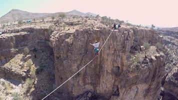 vue aérienne d'une femme en équilibre tout en marchant sur la corde raide et en slackline à travers un canyon. video