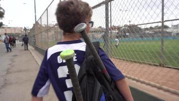A boy walks home after a little league baseball game. video