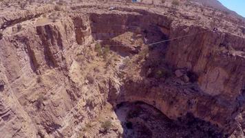 vue aérienne d'un homme en équilibre tout en marchant sur la corde raide et en slackline à travers un canyon. video