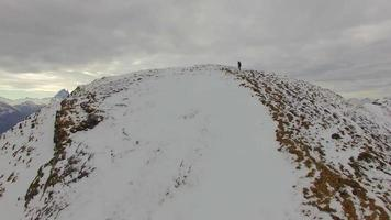 Aerial view of a trail runner running to the top of a snowy mountain. video