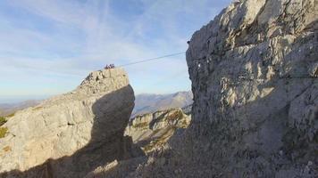 vue aérienne d'un homme en équilibre en slackline sur une corde raide dans les montagnes. video
