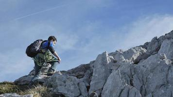 A man hiking with a backpack up a mountain. video