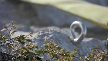 Detail of a carabiner being hooked onto a screweye preparing for slacklining the mountains. video