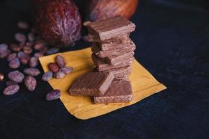 Granos de chocolate y cacao con cacao sobre un fondo negro foto